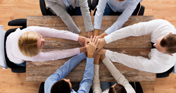 business, people, cooperation and team work concept - close up of creative team sitting at table and holding hands on top of each other in office